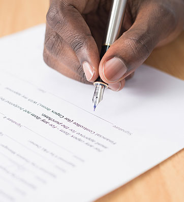 יד מחזיקה בעט חותמת על מסמך