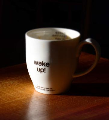 כוס קפה על שולחן עם כיתוב wake up