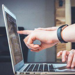 יד מצביעה על מסך מחשב נייד