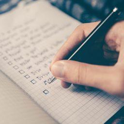 יד עם עד רושמת רשימה על מחברת משובצת
